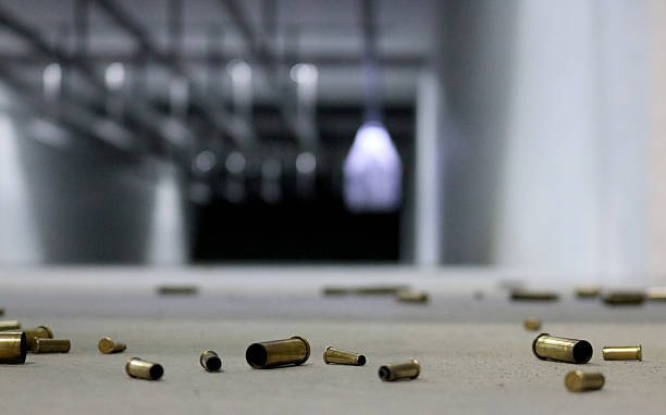 Spent Bullet Casings on the floor A variety of different shell casings spread across the floor at a shooting range with target in the background. ammunition stock pictures, royalty-free photos & images