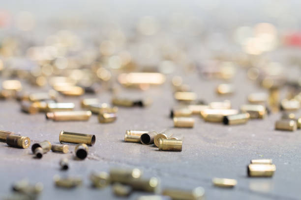 Spent shell casings. Spent shell casings on cement background. ammunition stock pictures, royalty-free photos & images