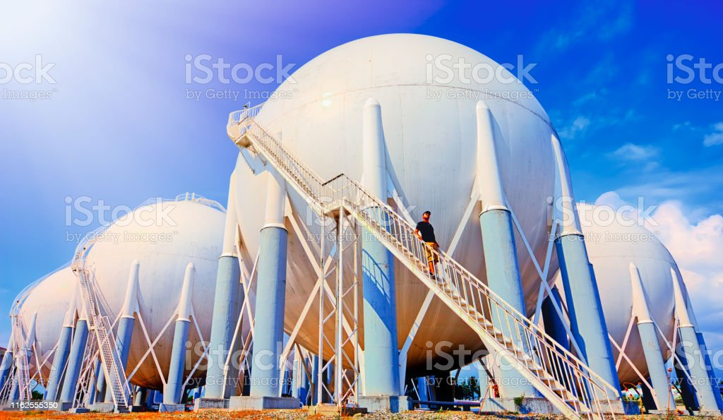 Sphere gas tanks in refinery plant and a worker on stairs