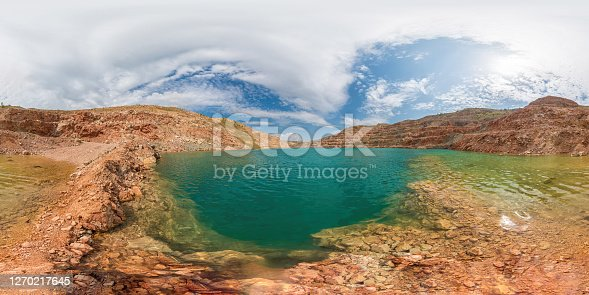 Emerald green lake in flooded opencast mine, open pit. Oval lake in mining industrial crater, acid mine drainage in rock. Open pit mine with lake. Quarry fluxes for the metal industry.