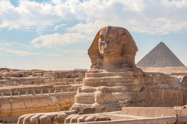 Sphinx monument against the background of large pyramids on a sunny day stock photo