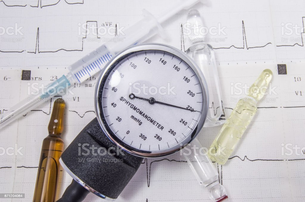 Sphygmomanometer with high levels of blood pressure, surrounded by different size vials, syringe on the background paper electrocardiogram. Urgent medical treatment for hypertensive emergency (crisis) stock photo