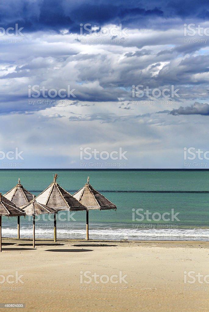 Spiaggia con ombrelloni e cielo drammatico: Pescara, Abruzzo, Włochy – zdjęcie
