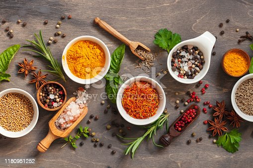 Spice and herb seasoning with fresh and dried herbs and spices in bowls on rustic wooden background. Flat lay. Top view.