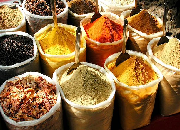 """spice market """"A spice vendor's display at a local market in south india: colorful, powdered spices in large sacks"""" garam masala stock pictures, royalty-free photos & images"""