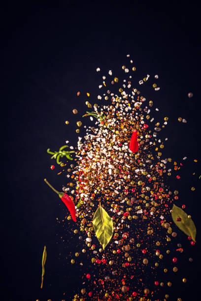 gewürz-mix essen explosion mit chili und pfeffer - speisesalz stock-fotos und bilder