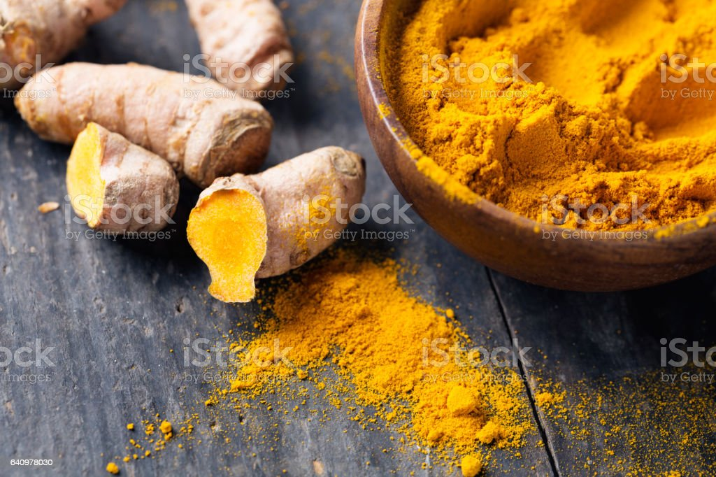 Spice: turmeric roots and powder on wood stock photo