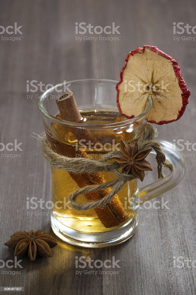 spiced apple cider in glass mug on wooden table, vertical royalty-free stock photo