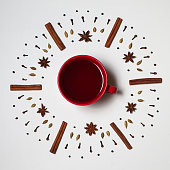 Flat lay of a cup of apple cider surrounded by a mandala of cinnamon sticks, star anise, cloves, and cardamom.