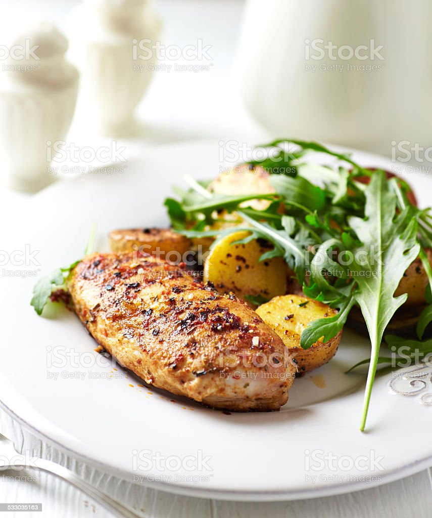 Spiced chicken breast with baked potatoes and arugula stock photo