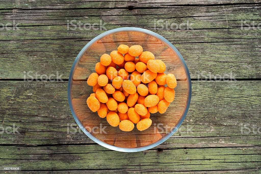 spiced coated fried peanuts in glass bowl on wooden background stock photo