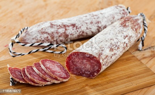 Close-up of spiced spanish longaniza sausages at wooden background