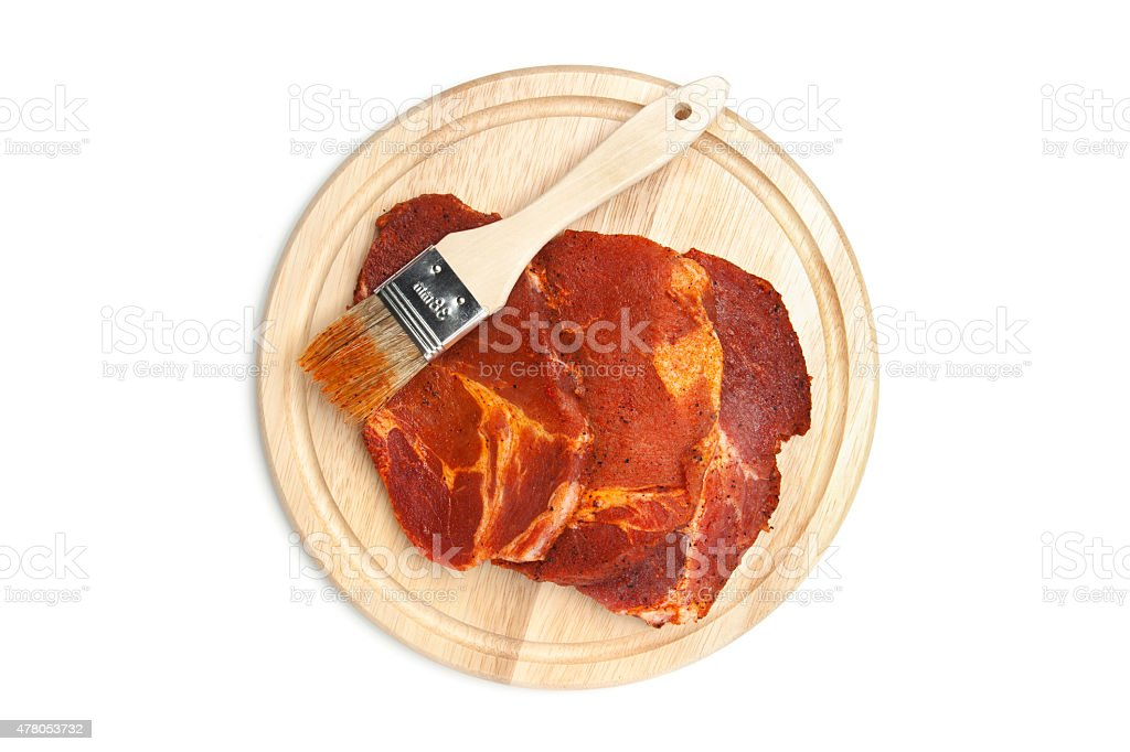 Spiced steaks on chopping board, brush stock photo
