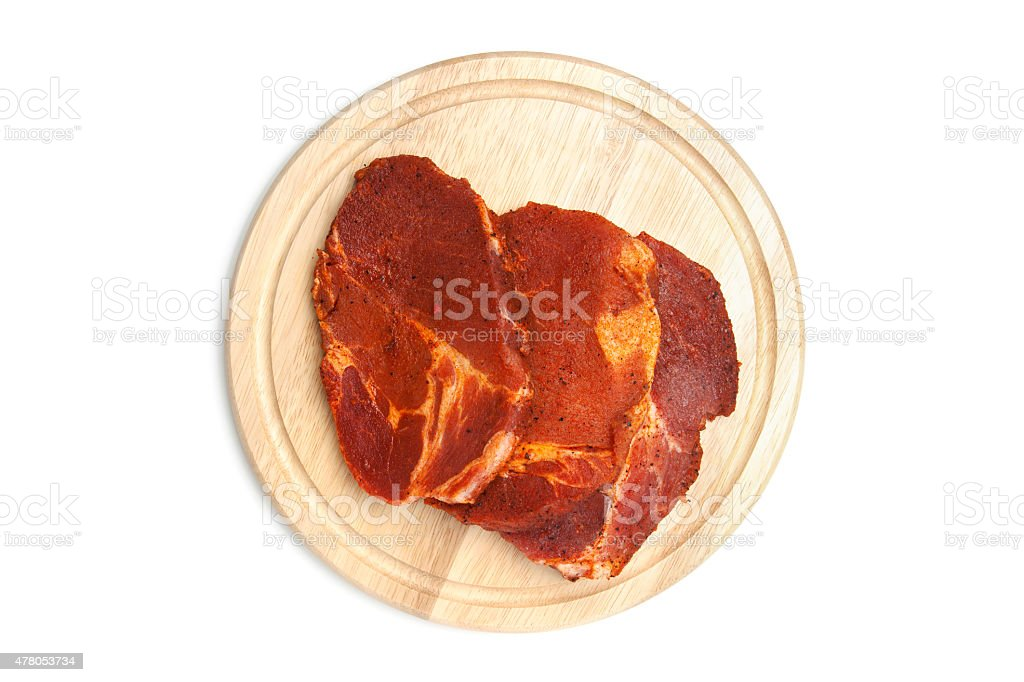 Spiced steaks on chopping board stock photo