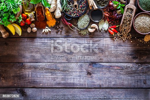 istock Spices and herbs border on rustic wood kitchen table 853872826