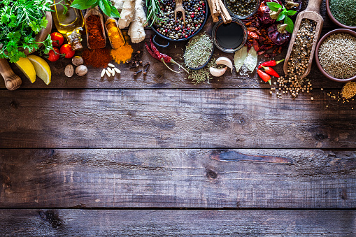 Top view of a rustic wood kitchen table with a large group of multi colored spices and herbs arranged in a row at the top border making a frame and leaving useful copy space for text and/or logo. Spices and herb included are clove, turmeric, bay leaf, cinnamon, olive oil, balsamic vinegar, curry powder, ginger, nutmeg, peppercorns, cinnamon, salt, chili pepper, basil, parsley, lemon, rosemary, garlic, onion and saffron. DSRL studio photo taken with Canon EOS 5D Mk II and Canon EF 100mm f/2.8L Macro IS USM