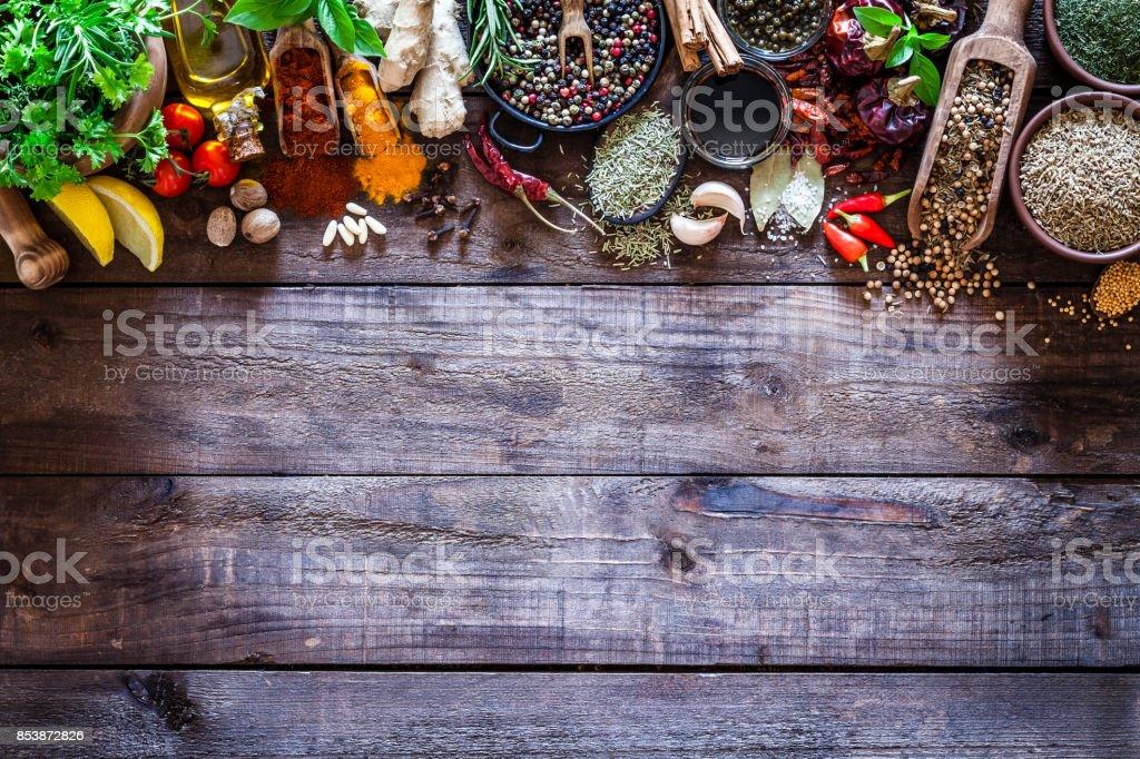 Kryddor och örter gränsen på rustika trä köksbord bildbanksfoto