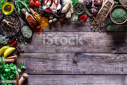 istock Spices and herbs border on rustic wood kitchen table 854359138