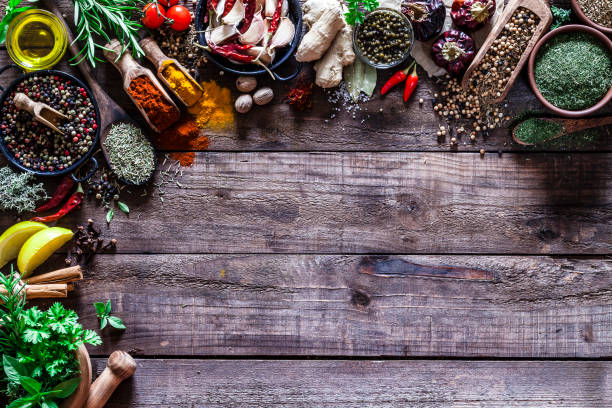 Spices and herbs border on rustic wood kitchen table stock photo