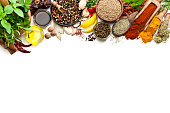 Top view of a large group of multi colored spices and herbs arranged in a row at the top border making a frame and leaving useful copy space for text and/or logo on white background. Spices and herb included are clove, turmeric, bay leaf, cinnamon, olive oil, balsamic vinegar, curry powder, ginger, nutmeg, peppercorns, cinnamon, salt, chili pepper, basil, parsley, lemon, rosemary, garlic, onion and saffron. DSRL studio photo taken with Canon EOS 5D Mk II and Canon EF 100mm f/2.8L Macro IS USM