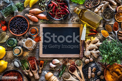 Top view of a rustic wood kitchen table with a large group of multi colored spices and herbs placed all around a blank blackboard leaving useful copy space for text and/or logo. Spices and herb included are clove, turmeric, star anise, bay leaf, cinnamon, curry powder, ginger, nutmeg, peppercorns, cinnamon, salt, chili pepper, cardamom, dried oregano, basil, parsley, lemon, rosemary, garlic, onion and dried orange slices. An olive oil bottle is included in the composition as well as a closed cookbook. DSRL studio photo taken with Canon EOS 5D Mk II and Canon EF 70-200mm f/2.8L IS II USM Telephoto Zoom Lens