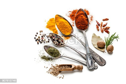 Top view of four old spoons with spices and herbs shot on white background. Spices and herb included are turmeric, bay leaf curry powder, nutmeg, peppercorns, paprika, mustard seeds and others. High key DSRL studio photo taken with Canon EOS 5D Mk II and Canon EF 100mm f/2.8L Macro IS USM