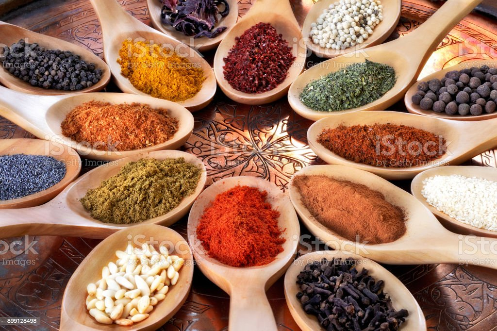 Spices and herbs in wooden spoons. stock photo