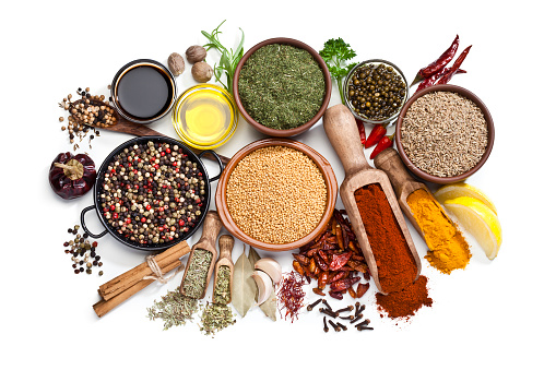 Top view of a large group of multi colored spices and herbs in bowls, wooden serving scoops or placed directly on the table shot on white background. Spices and herb included are clove, turmeric, bay leaf, cinnamon, olive oil, curry powder, nutmeg, peppercorns, chili pepper, basil, parsley, lemon, rosemary, garlic and saffron. DSRL studio photo taken with Canon EOS 5D Mk II and Canon EF 100mm f/2.8L Macro IS USM