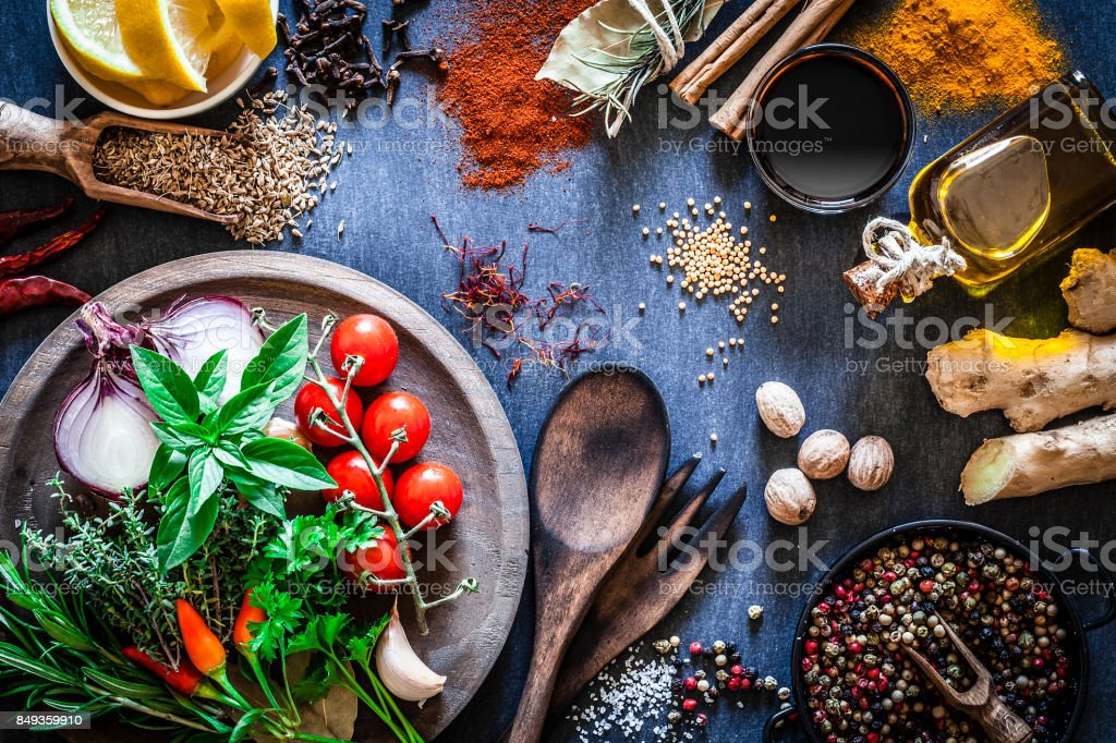 Spices and herbs on dark kitchen table stock photo