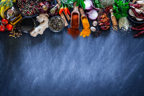 spices and herbs on dark kitchen table - pepper seasoning stock photos and pictures