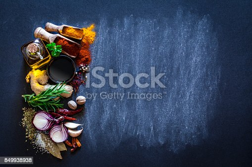 Top view of a dark bluish background with a large group of multi colored spices and herbs arranged in a row at the left leaving useful copy space for text and/or logo at the right. Spices and herb included are clove, turmeric, bay leaf, cinnamon, olive oil, balsamic vinegar, curry powder, ginger, nutmeg, peppercorns, cinnamon, salt, chili pepper, basil, parsley, lemon, rosemary, garlic, onion and saffron. DSRL studio photo taken with Canon EOS 5D Mk II and Canon EF 100mm f/2.8L Macro IS USM