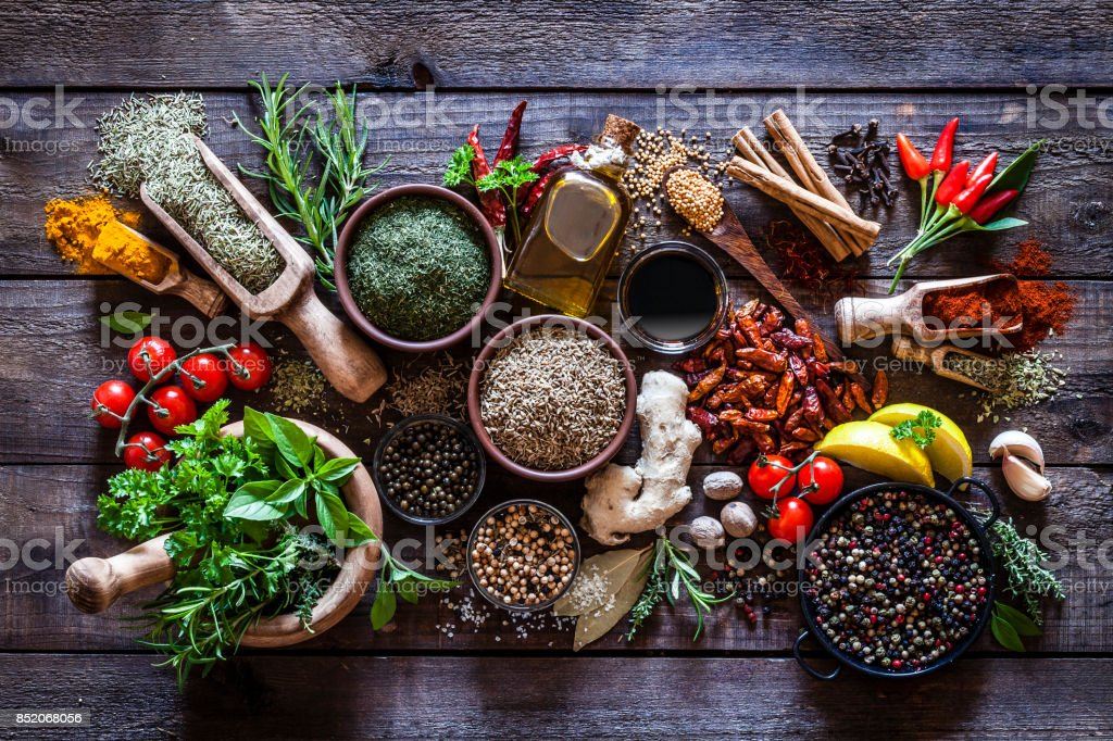 Spices and herbs on rustic wood kitchen table
