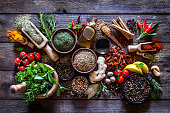 Top view of a rustic wood kitchen table filled with a large group of multi colored spices and herbs in bowls, wooden serving scoops or placed directly on the table. Spices and herb included are clove, turmeric, bay leaf, cinnamon, olive oil, curry powder, ginger, nutmeg, peppercorns, cinnamon, salt, chili pepper, basil, parsley, lemon, rosemary, garlic, onion and saffron. Low key DSRL studio photo taken with Canon EOS 5D Mk II and Canon EF 100mm f/2.8L Macro IS USM