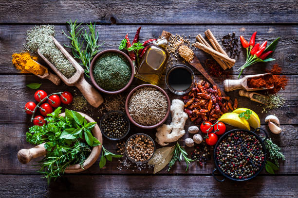 Spices and herbs on rustic wood kitchen table stock photo