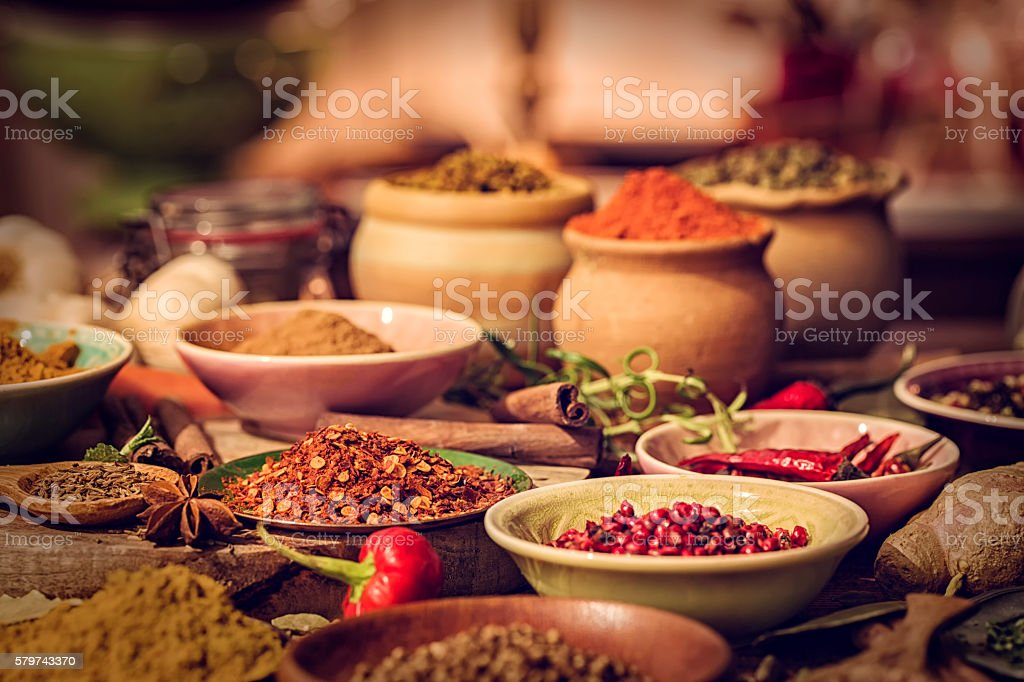 Spices and Herbs on Wooden Background Variation of Spices and Herbs like chili peppers, parsley, rosemary, peppercorns, cayenne pepper, tumeric, cumin, garlic and ginger on wooden background Backgrounds Stock Photo