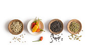 Group of bowls containing different exotic spices and properly isolated on a white background, with the focus on the wooden bowl with red chilis. Studio shot with nice shadow.