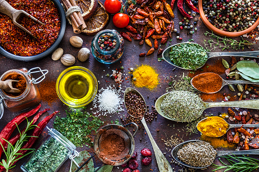 Top view of a rustic brown table filled with a large group of multi colored spices and herbs placed directly on the table. Spices and herb included are clove, turmeric, bay leaf, cinnamon, curry powder, nutmeg, peppercorns, salt, chili pepper, cardamom, dried oregano, parsley, rosemary and dried orange slices. An olive oil bowl is included in the composition. DSRL studio photo taken with Canon EOS 5D Mk II and Canon EF 70-200mm f/2.8L IS II USM Telephoto Zoom Lens