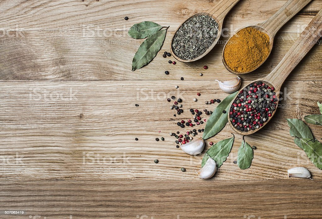 Spices and herbs. Spice greens in spoons on wooden background. stock photo