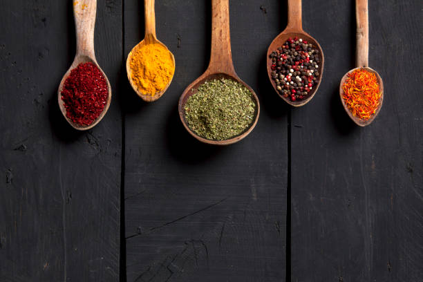 Spices and herbs with old wooden spoons on wooden background stock photo