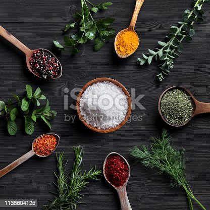 Spices and herbs with old wooden spoons on wooden background