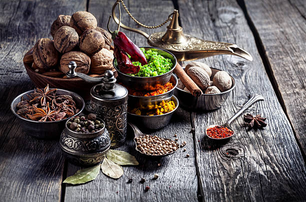 Spices and nuts at wooden table​​​ foto