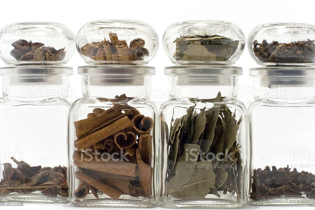 Spices in bottles on white: anise, cloves, cinnamon, bayleaf royalty-free stock photo