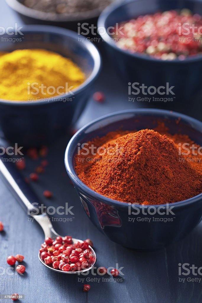 spices in bowls: curry, pink and black pepper, paprika powder royalty-free stock photo
