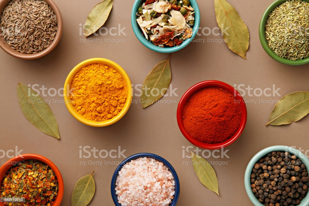 Spices in colorful bowls viewed from above. Various seasonings on a dark background. Italian mix, cumin, chili pepper, curry powder, Himalayan salt, pepper, garlic, cinnamon, dried tomato. Top view stock photo