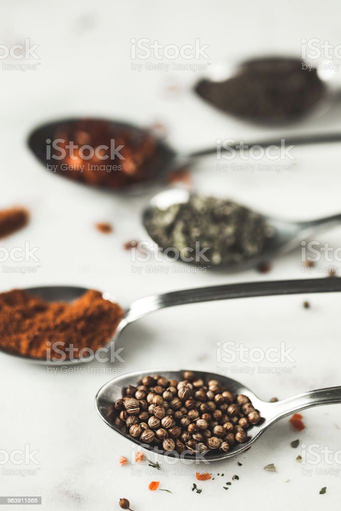 Spices in different spoons on stone marble table background. Rustic vintage color toning - Royalty-free Arabia Stock Photo
