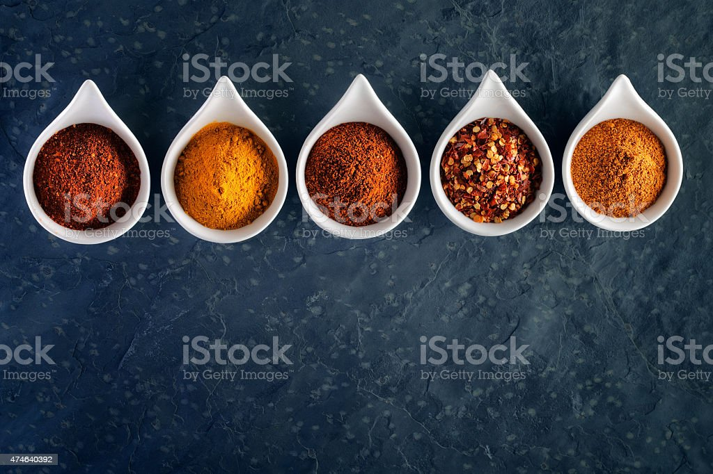 Spices in spoons on dark slate stock photo