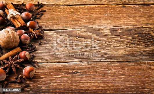 istock Spices on a old wooden background. Cinnamon, nuts, anise, clove. 1069203848