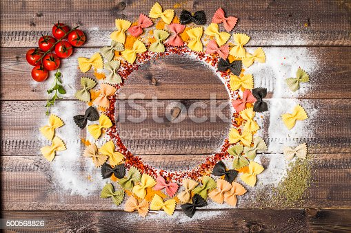 colorful spices and farfalle on wooden table with cutlery silhouette, top view