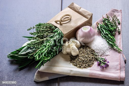 istock Spices: rosemary, thyme, oregano, sea salt, herbs in a paper bag, garlic and onion 945032950