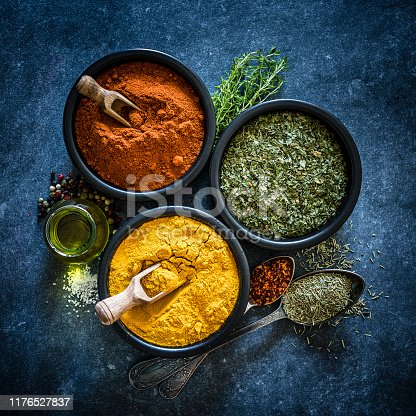 Spices: Indian food. Ground turmeric, chili pepper and dried parsley in black bowls shot from above on dark bluish tint table.  Low key XXXL 42Mp studio photo taken with SONY A7rII and Zeiss Batis 40mm F2.0 CF